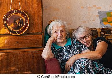 un, mujer anciana, con, ella, adulto, hija, sentado, en, un, abrazo, en, el, couch.