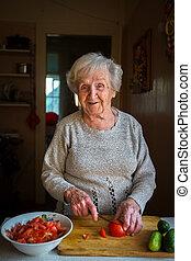 un, mujer anciana, corta, vegetales, para, un, ensalada, en, el, kitchen.