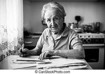 un, mujer anciana, llena, el, cuenta, para, pago, de, utilidad, services.
