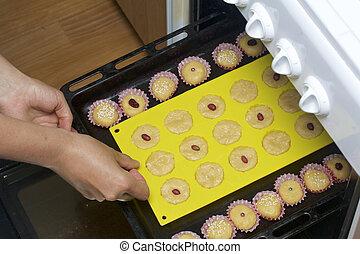 un, mujer, pone, un, bandeja de la hornada, en, el, horno, con, billets, para, un, cupcake.