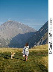 un, niña, es, ambulante, con, un, perro, en las montañas