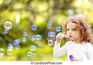 un, niña, soplar jabón burbujea, primer plano, retrato, hermoso, rizado, baby.