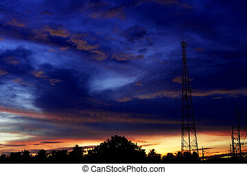 un, silueta, de, el, antena, y, líneas de alimentación, contra, un, dramático, y, colorido, cielo, en, salida del sol, o, sunset.