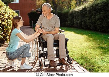 un, uomo anziano, è, seduta, in, uno, wheelchair., il, ragazza, accoccolato, accanto, lui, lei, osservare, him.