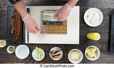 Unagi sushi roll preparation. Hands making food, wooden...