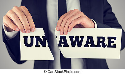 Unaware - Businessman tearing up a sign saying - Unaware -...