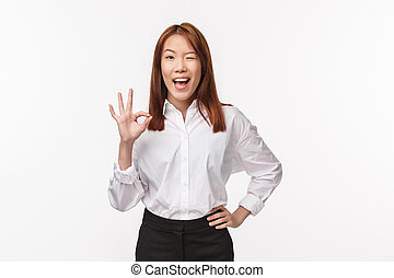 Unbothered cheerful pretty asian woman in white shirt, show okay gesture, confirm work done, wink and smiling happy, assure all good, everything perfect, excellent job, white background