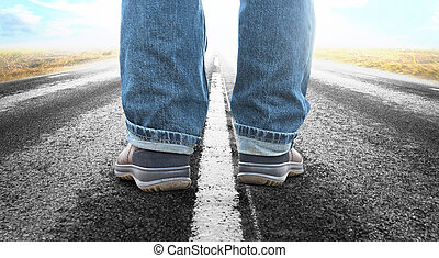 Close up of feet of man on long straight asphalt road