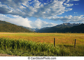 Mountain valley near Ridgway, Colorado with the San Juan Mountain range in the background and a dramatic sky