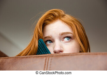 Unconfident shy redhead girl peeping from sofa - Unconfident...