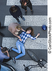 Unconscious biker lying on the road after car crash