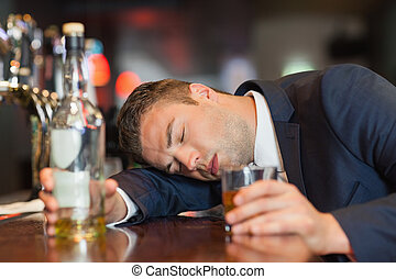 Unconscious businessman holding whiskey glass lying on a ...
