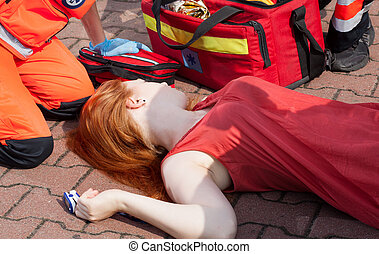 Unconscious girl lying on street with pulse oximeter on...