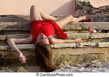 unconscious on the stairs - woman playing dead, lying on the...