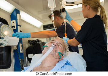 Unconscious patient with oxygen mask in ambulance