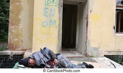 Unconscious sleeper - Tilt down of a vagabond sleeping or...