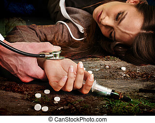Unconscious woman addicted keeps syringe and lying on  dirty floor.