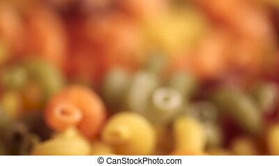 uncooked colorful pasta scattered as background. blurred...