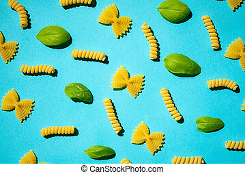 Uncooked curly pasta and basil leaf pattern on blue background. Traditional dry raw macaroni pattern. Nobody