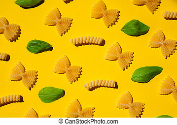 Uncooked curly pasta and basil leaf pattern on yellow background. Traditional dry raw macaroni pattern. Nobody