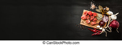 Uncooked fresh diced beef meat with herbs and oil on an old rustic wooden kitchen board over black background. Top view with free space for text. Banner