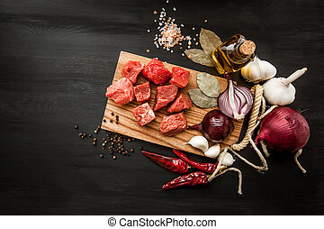 Uncooked fresh diced beef meat with herbs and oil on an old rustic wooden kitchen board over black background. Top view with free space for text.