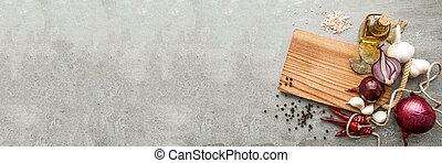 Uncooked fresh diced beef meat with herbs and oil on an old rustic wooden kitchen board over stone background. Top view with free space for text. Banner