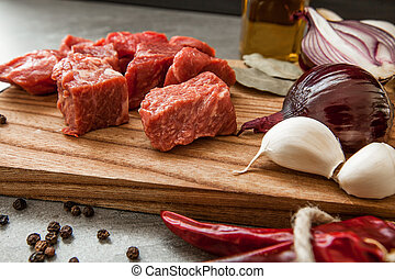 Uncooked fresh diced beef meat with herbs and oil on an old rustic wooden kitchen board over stone background.