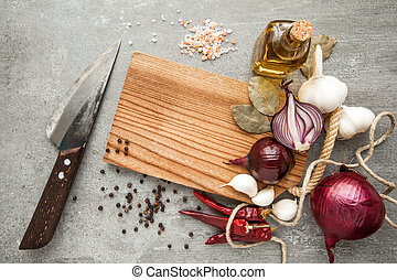Uncooked fresh diced beef meat with herbs and oil on an old rustic wooden kitchen board over stone background. Top view with free space for text.