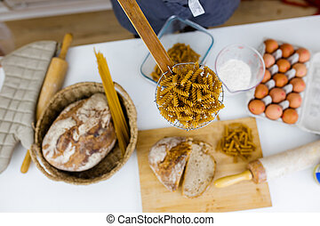 Uncooked fusilli on wooden pasta strainer above ingredients on a table