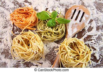 Uncooked italian pasta in three colors
