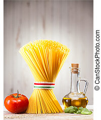 Uncooked dried Italian spaghetti tied with a ribbon in the colours of the national flag - red, white and green, standing upright on a kitchen counter with fresh tomato and basil and a jar of olive oil