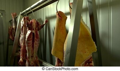 Uncooked meat hanging on hooks. Fresh pork meat hanging on...