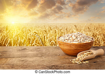uncooked oat flakes in bowl on table