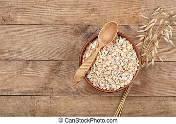 Uncooked oatmeal in bowl and oat ear