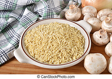 Uncooked orzo pasta with mushrooms and onions