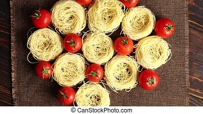 Uncooked pasta bunches and tomatoes - Top view of arranged...