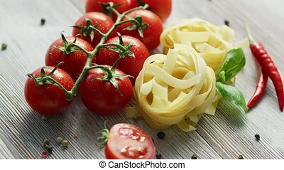 Uncooked pasta bunches with tomatoes - Raw small heaps of...