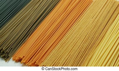 Uncooked pasta in row - Multicolored organic uncooked...