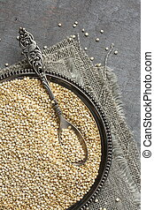 Uncooked quinoa in metal plate on wooden background