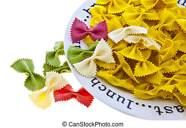 Uncooked rainbow farfalle pasta spilling from plate on white background with copy space.