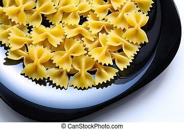 Uncooked raw Farfalle on black ceramic plate