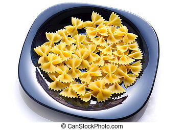 Uncooked raw Farfalle on black ceramic plate.