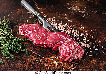 Uncooked Raw flank beef steak on meat fork. Dark background. Top view