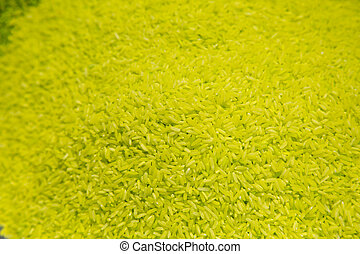 Uncooked raw yellow rice grains background texture