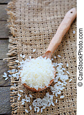 uncooked rice on wooden spoon, food close uo