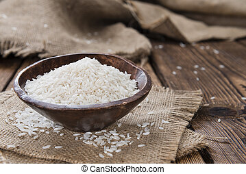 Uncooked Rice - Portion of uncooked Rice on rustic wooden...