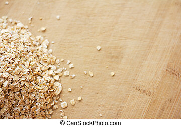Heap of uncooked oats on a wooden chopping board. Image contains copy space.