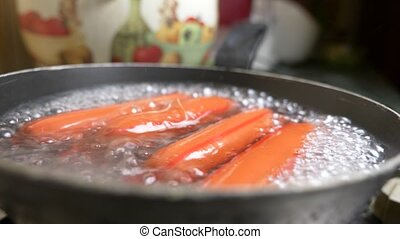 uncooked sausages are boiled in water on a gas stove. 4k,...