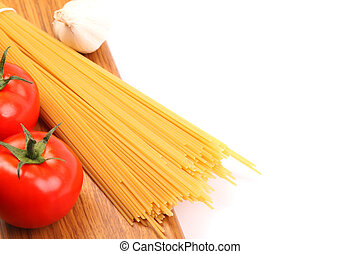 uncooked spaghetti and tomatos on a white background